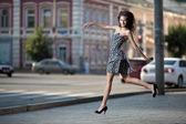 Zorgeloos jongedame springen op de straat in de stad — Stockfoto