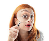 Young woman looking through a magnifying glass — Stock Photo