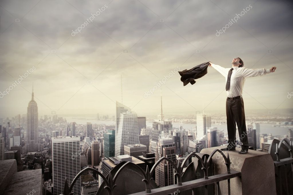 Happy businessman standing on the rooftop of a skyscraper — Zdjęcie stockowe #5752685