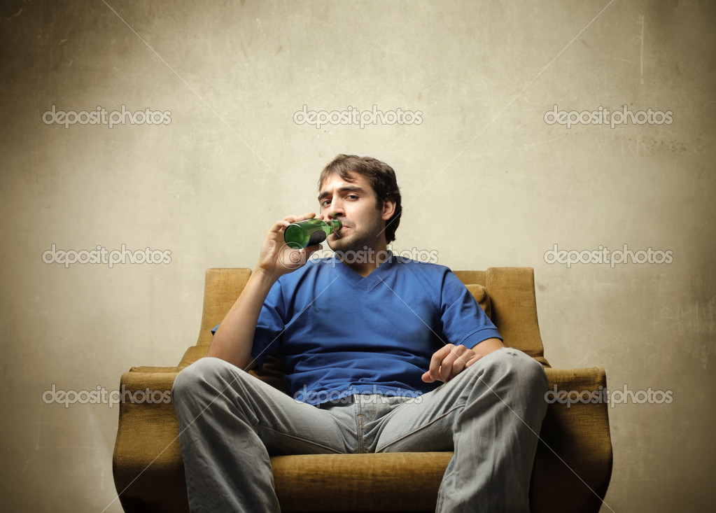 Young man sitting on an armchair and drinking a bottle of beer — Stock Photo #5752805