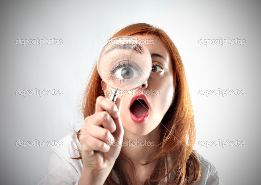Astonished woman looking through a magnifyin glass — Stock Photo #5757106