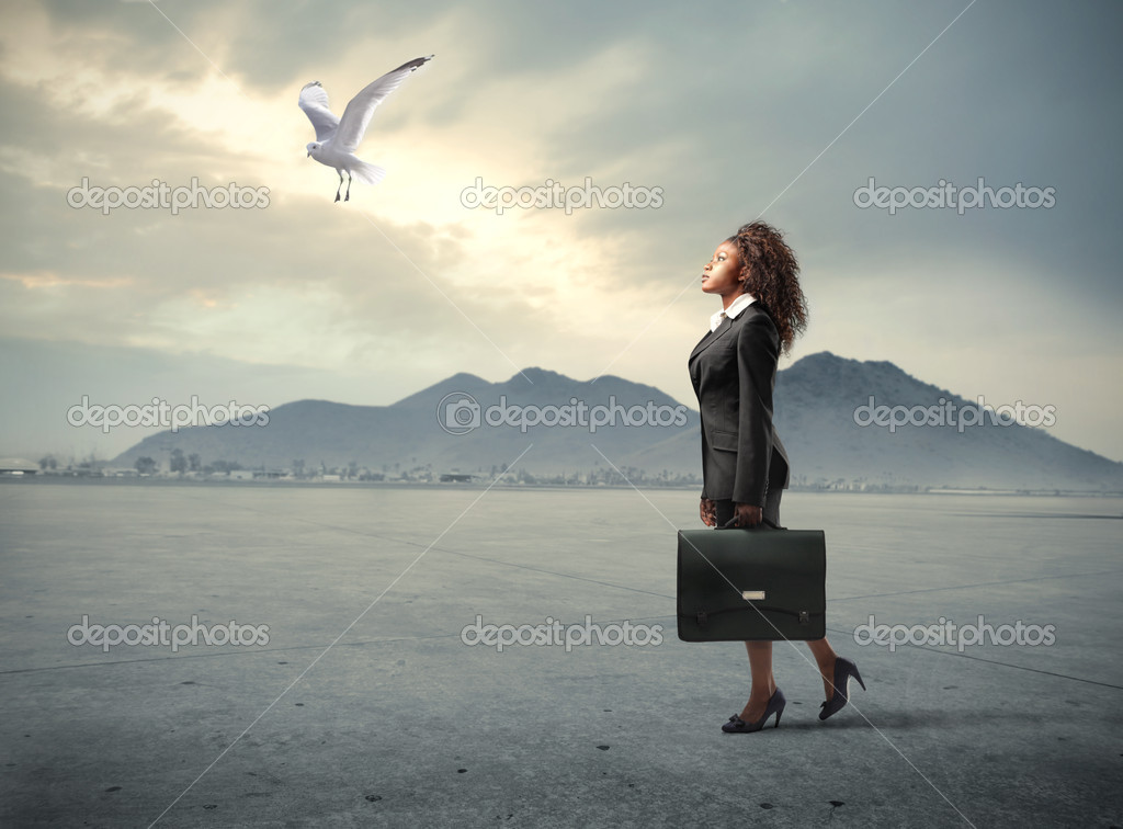 African woman walking in a desert with seagull flying in front of her — Stock Photo #5757480