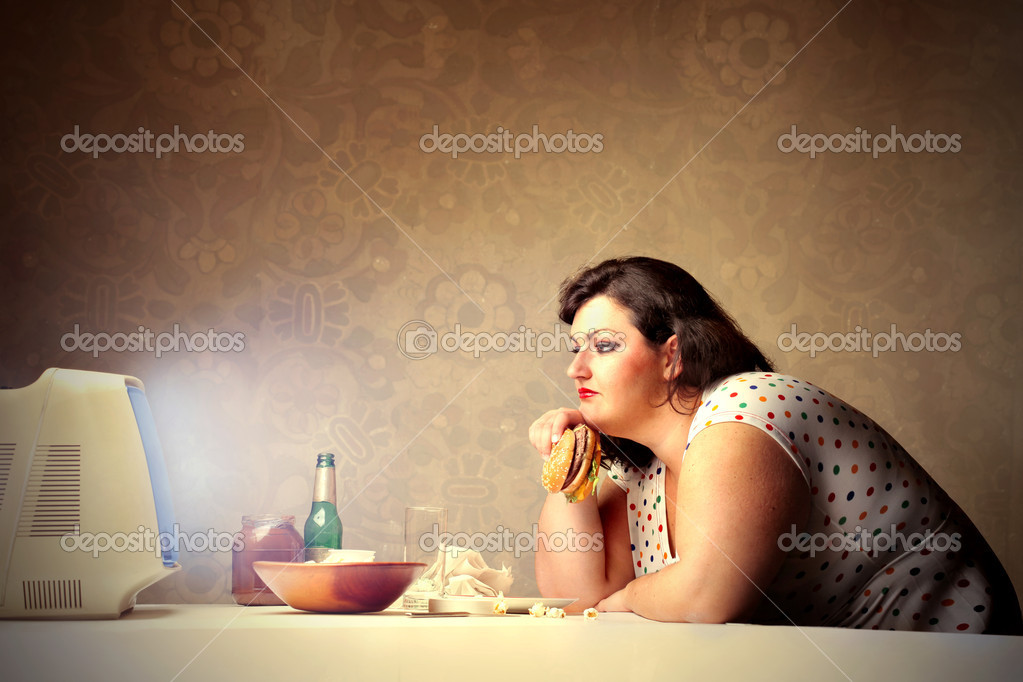 Fat woman eating hamburger and drinking beer while watching television — Stock Photo #5757783