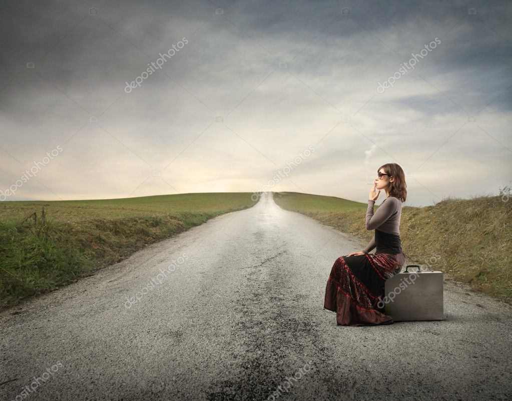 Elegant woman sitting on a suitcase and smoking a cigarette on a countryside road — Foto Stock #5757872