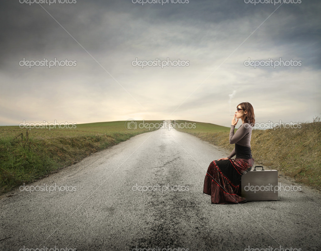 Elegant woman sitting on a suitcase and smoking a cigarette on a countryside road — Stockfoto #5757872