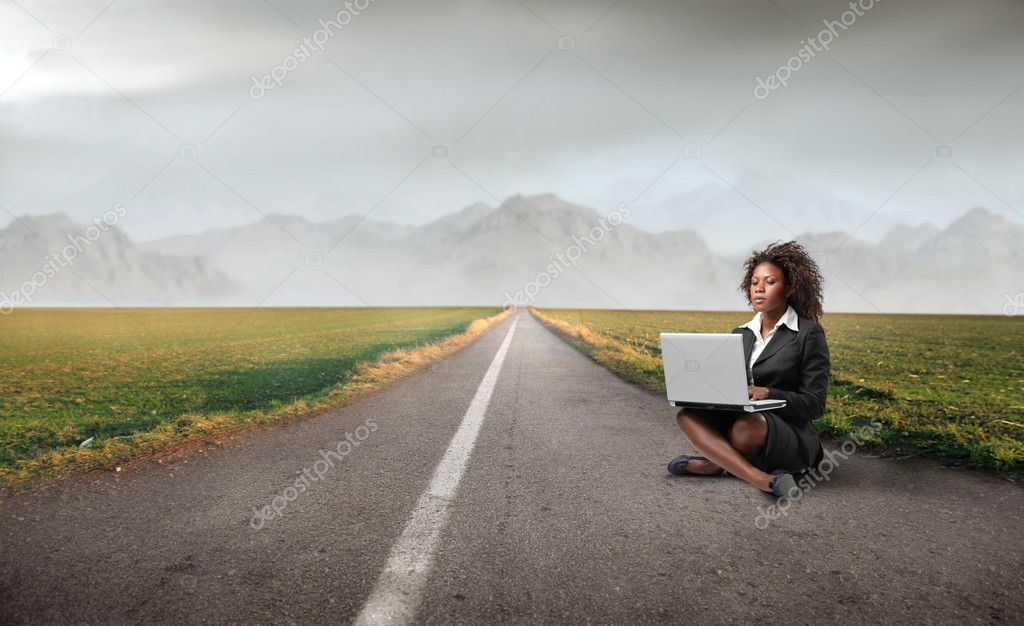 African businesswoman sitting on a countryside road and using a laptop  Stock Photo #5758628