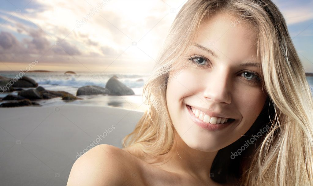 Smiling beautiful woman with seaside in the background — Stock Photo #5759724