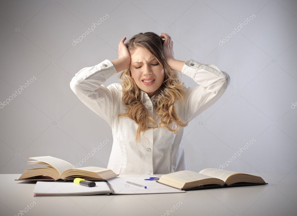 Beautiful student with painful expression looking at the books she is studying — Stock Photo #5762707