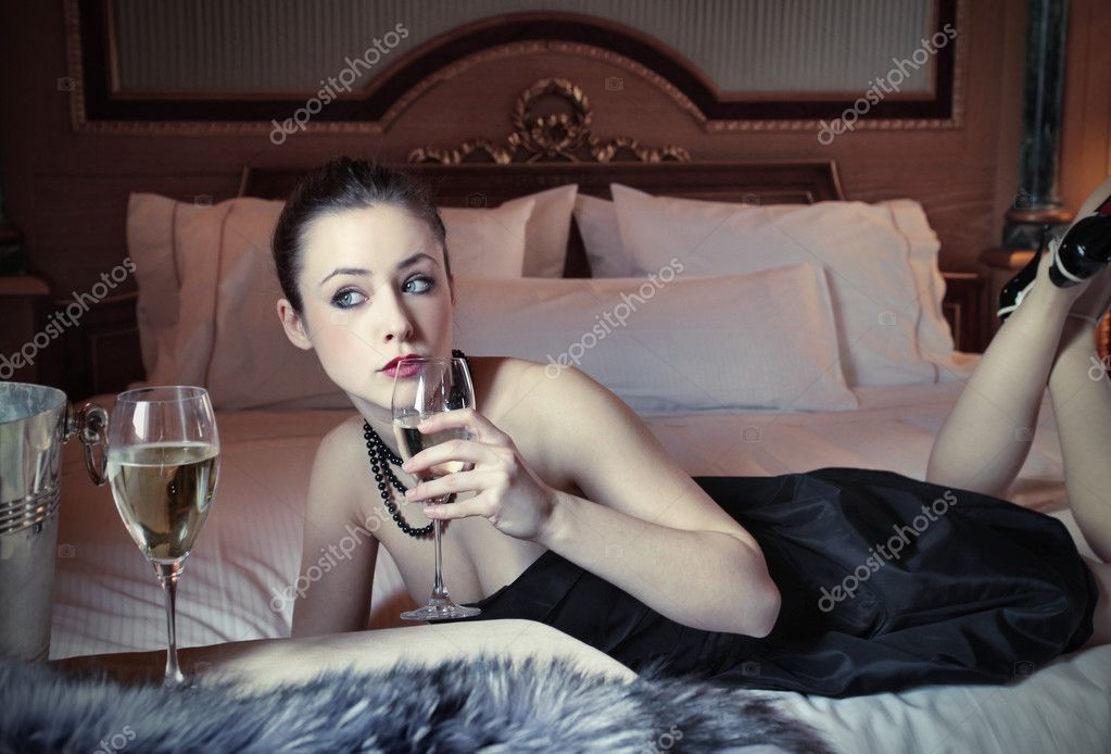Beautiful woman lying on a bed in a luxury hotel room and drinking a glass of wine — Stock Photo #5946481