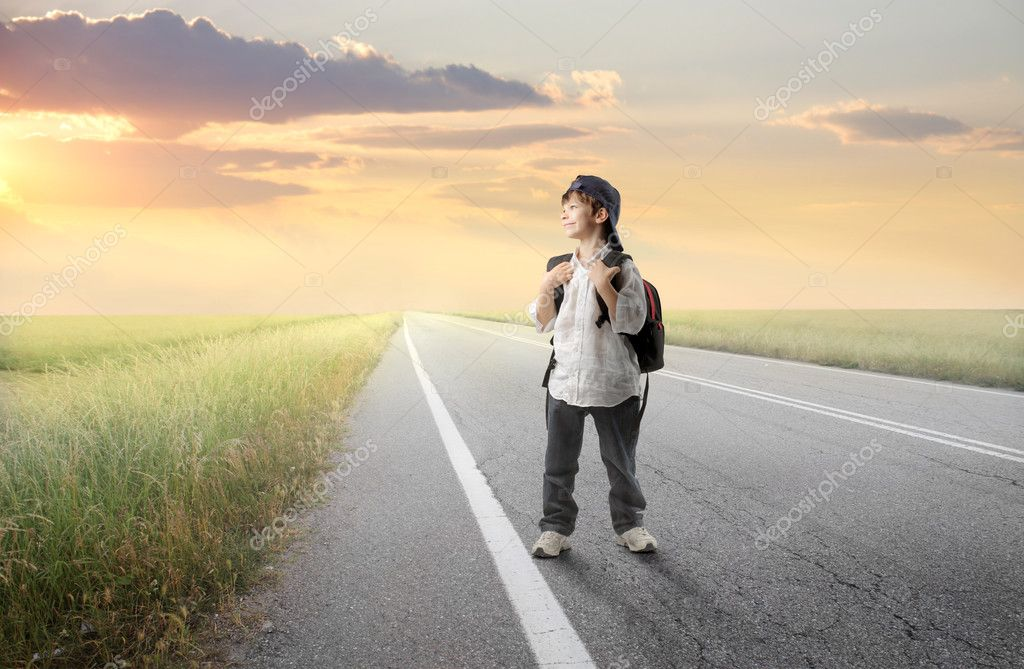 Smiling child with backpack on a countryside road  Stock Photo #5946546