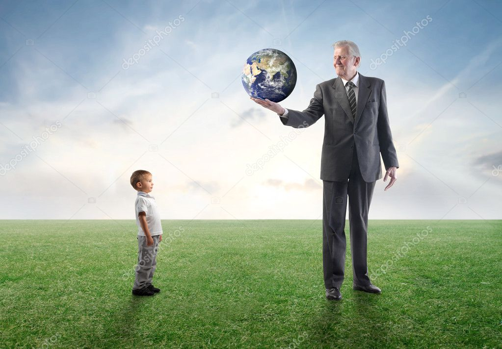 Senior businessman lending the Earth to a child  Stock Photo #5947126