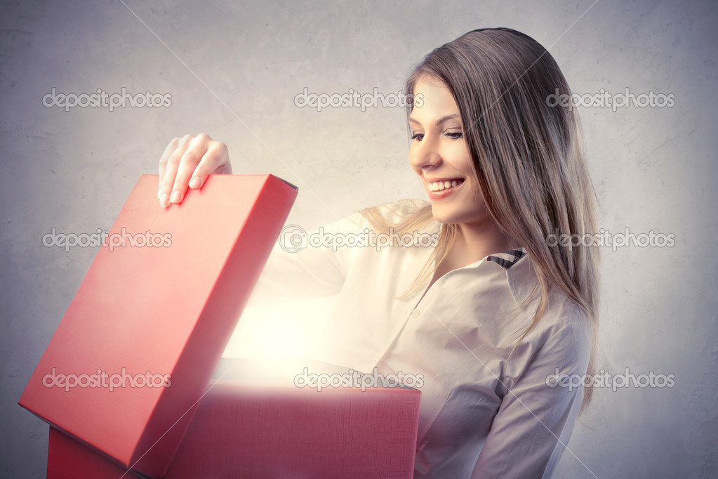 Smiling beautiful woman opening a present — Stock Photo #5947513
