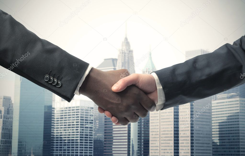 African and white businessman shaking hands with cityscape in the background — Stock Photo #5948542