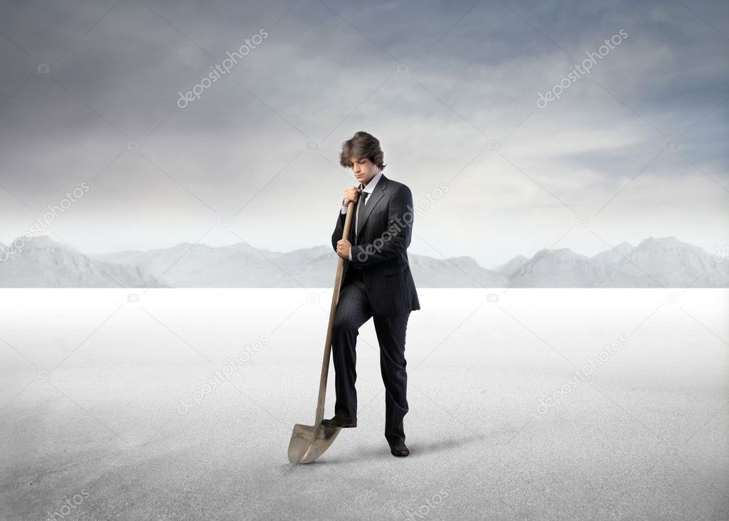 Businessman digging with a shovel in a desert — Stock Photo #5950819