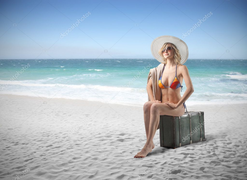 Beautiful woman in bikini sitting on a suitcase at the seaside — Stock Photo #5950910