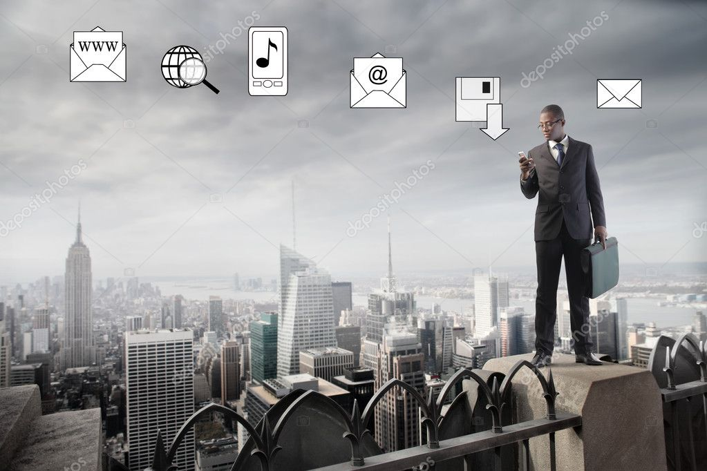 African businessman using a mobile phone from the rooftop of a skyscraper with communication symbols in the background — Stock Photo #5970223
