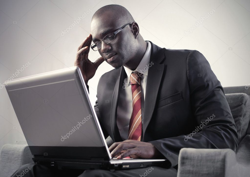 Concentrated african man using a laptop — Stock Photo #5972435