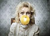 Senior woman blowing a bubblegum — Stock Photo