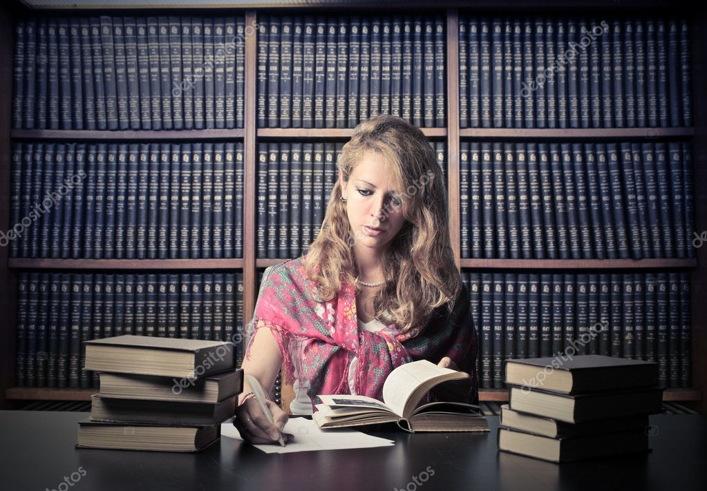 Beautiful woman sitting in a library and studying — Stock Photo #6308662