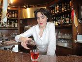 Female bartender serving an aperitif in a bar — Stock Photo