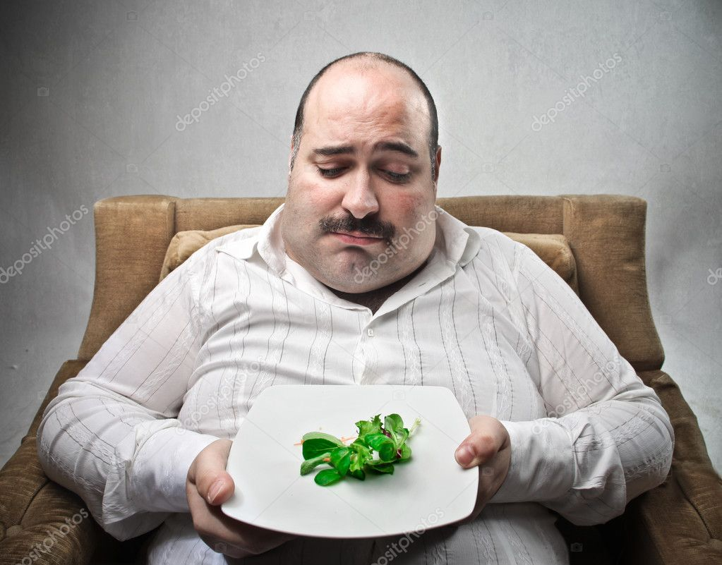Sad fat man looking at his dish containing barely salad — Stock Photo #6310209