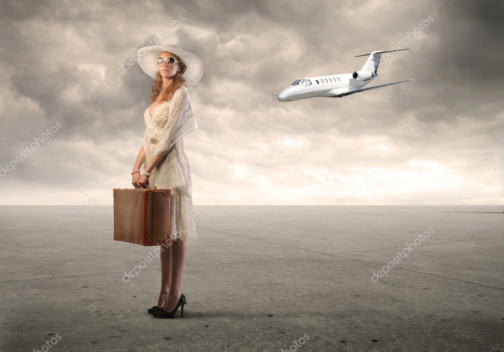 Young woman holding a suitcase with airplane in the background — Stock Photo #6312602