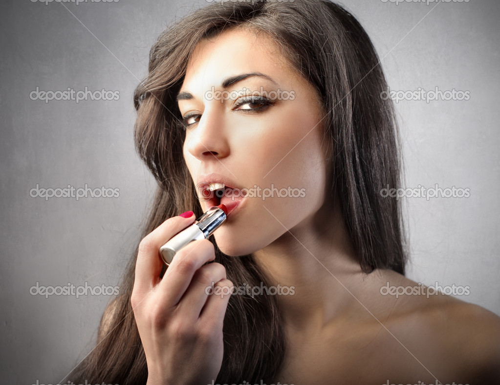 Beautiful woman putting on some lipstick — Stock Photo #6312828