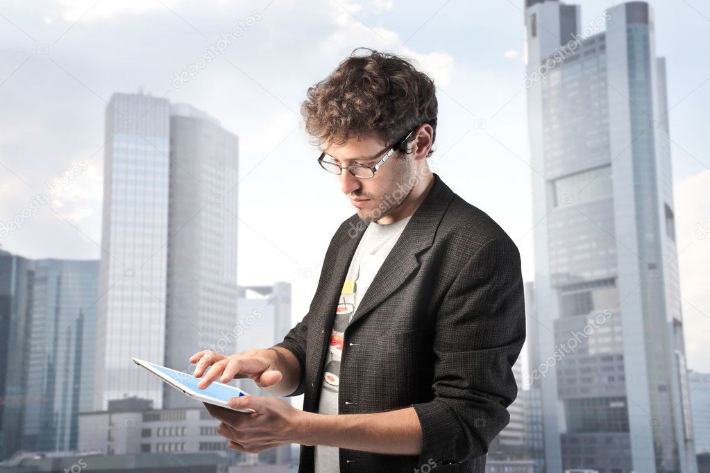 Young man using a tablet pc with cityscape in the background — Stock Photo #6315606