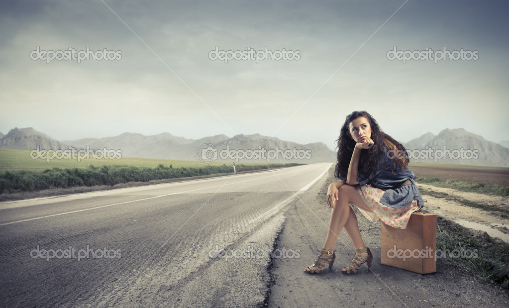 Beautiful woman sitting on a suitcase by a countryside road  Stock Photo #6321929