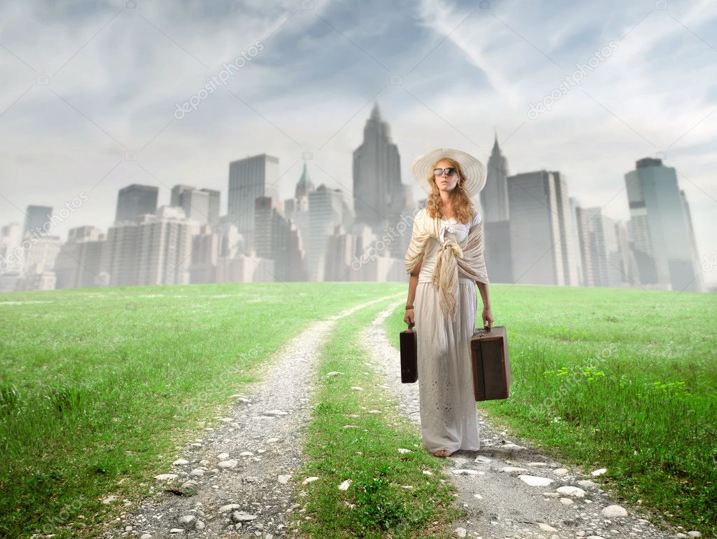 Beautiful woman walking away from a city — Stock Photo #6322269