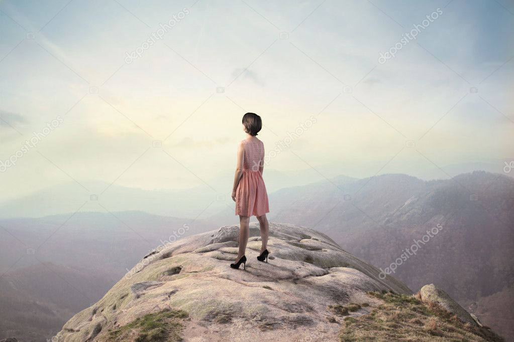 Beautiful woman on a peak over the mountains  Stock Photo #6322363