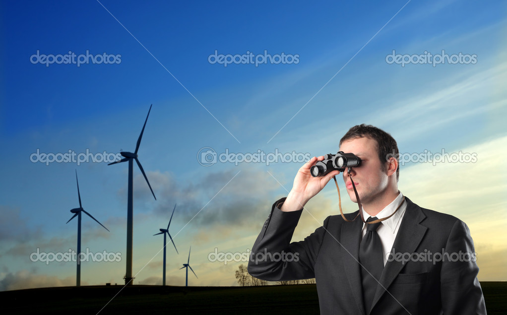 Businessman using binoculars and wind turbines in the background — Stock Photo #6322570