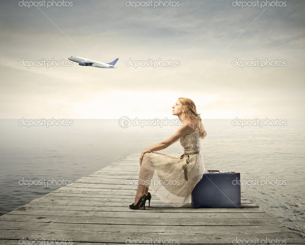 Beautiful woman sitting on a suitcase on a pier with airplane in the background  Foto Stock #6325679