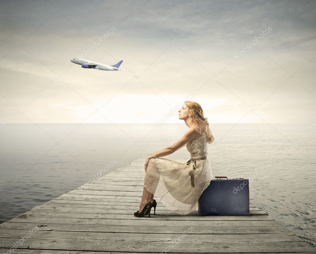 Beautiful woman sitting on a suitcase on a pier with airplane in the background — Stok fotoğraf #6325679