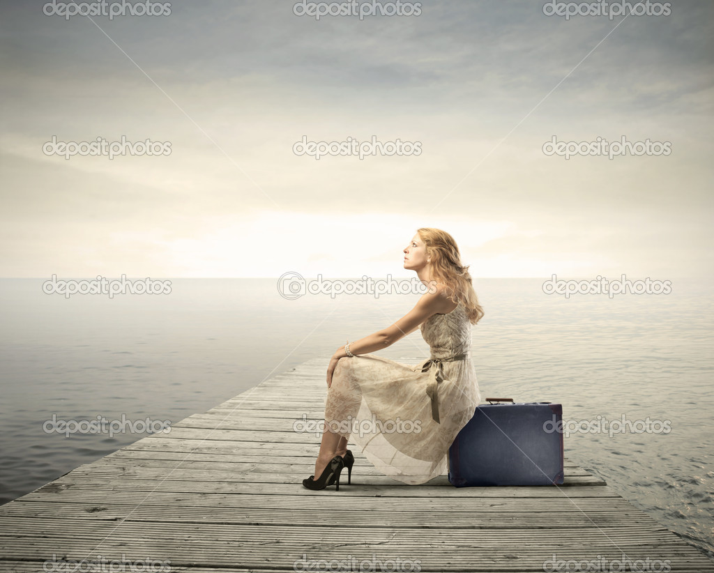 Beautiful woman sitting on a suitcase on a pier — Stock fotografie #6325776