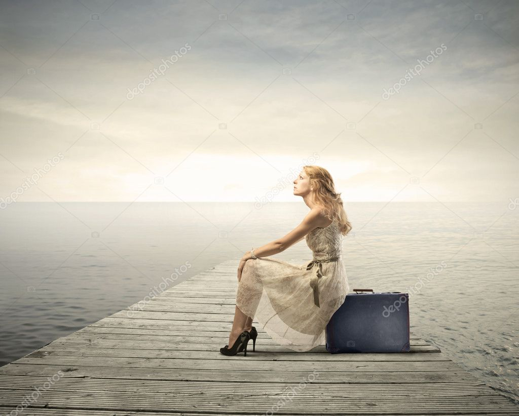 Beautiful woman sitting on a suitcase on a pier — Photo #6325776