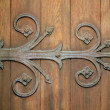 Stock Photo: Ornamental Iron Hinge On Old Wooden Door