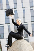 Sitting young businesswoman with a briefcase — Stock Photo