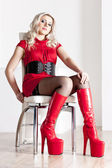 Sitting young woman wearing extravagant boots — Stock Photo