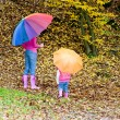 Mother and her daughter with umbrellas in autumnal nature — Stock Photo