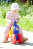 Little girl on toy motorcycle — Stock Photo