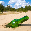 Green glass bottle in sands — Stock Photo