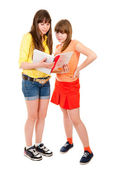 Two schoolgirls teenagers read something in a notebook — Stock Photo