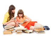 Two schoolgirls read many books — Stock Photo