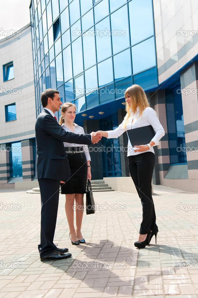 Business shaking hands in a modern downtown  Stock Photo #5635728