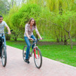 Happy young couple riding bicycles — Stock Photo