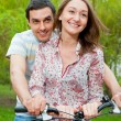 Happy young couple riding bicycles - Stock Photo