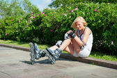 Blonde woman has hit a knee skating on roller-skaters — Stock Photo