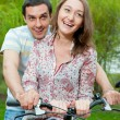 Happy young couple riding bicycle — Stock Photo