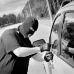 Thief breaks into a car door — Stock Photo